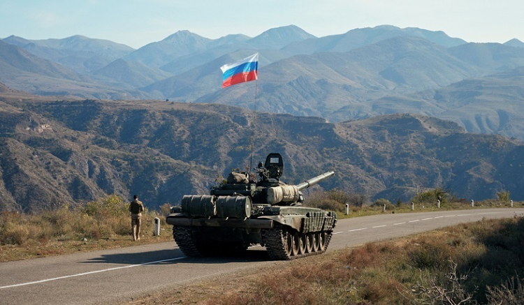 A service member of the Russian peacekeeping troops walks near a tank near the border with Armenia, following the signing of a deal to end the military conflict between Azerbaijan and ethnic Armenian forces, in the region of Nagorno-Karabakh, November 10, 2020. REUTERS/Francesco Brembati